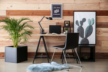 Stylish workplace with modern computer near wooden wall