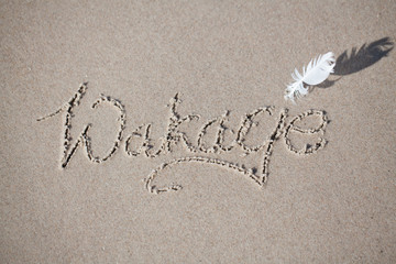"Polish inscription on the beach ""wakacje"". holiday, beach, inscription on the sand,"
