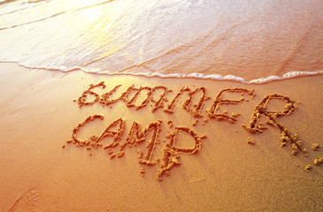 Summer camp letters handwritten in sand on beach