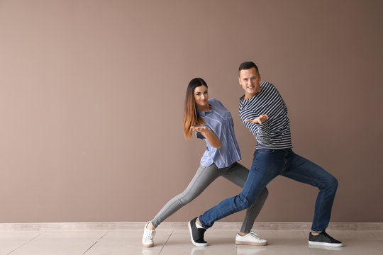 Couple of young dancers near color wall