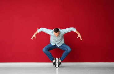 Young man dancing near color wall