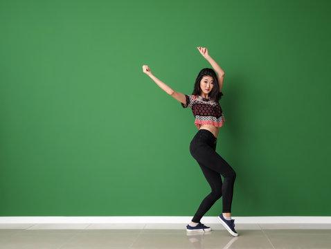 Female Asian dancer near color wall
