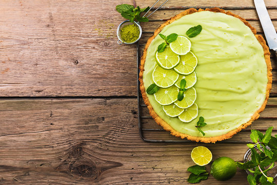 Key Lime Pie with several limes and mint over wooden background, top view with copy space.