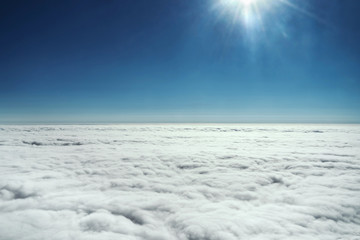 Clear view of the sky with clouds and sun from the plane.