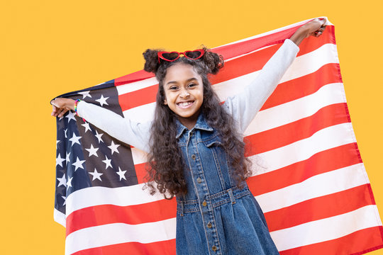 Cheerful delighted girl holding up a US flag