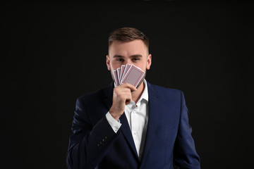 Handsome man with cards on dark background