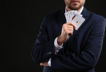 Handsome man with cards on dark background