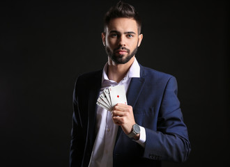 Handsome young man with cards on dark background