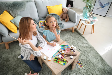 Happy mother with daughter painting at home