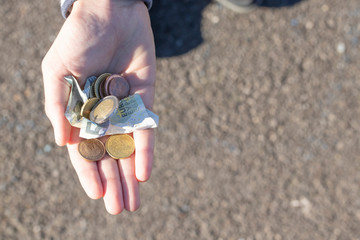 A child holds coins and euro notes in his hands. Pocket money image.