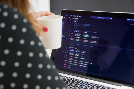 Woman programmer with cup of coffee working on laptop computer in office