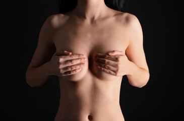 Young woman with beautiful breast on dark background