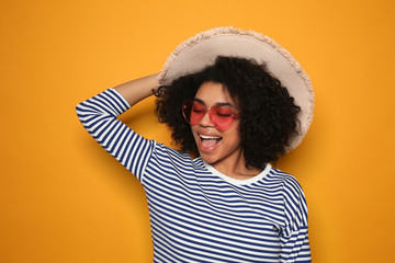 Portrait of young African-American woman on color background