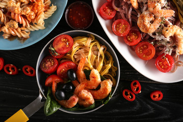 Plates with different pasta on table, top view