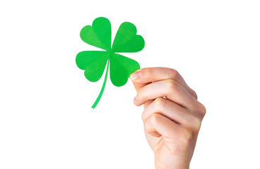 fortune, luck and st patricks day concept - hand holding green paper shamrock over gray background