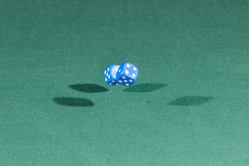 Two blue dices falling on a green table