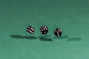 Three black dices falling on a green table