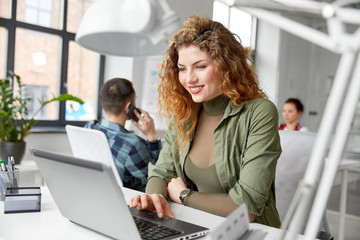 business, startup, education and people concept - happy young woman with computer working at office