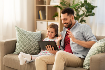family, fatherhood and technology concept - happy father and little daughter having video call on tablet pc computer at home