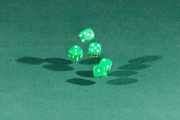 Five green dices falling on a green table