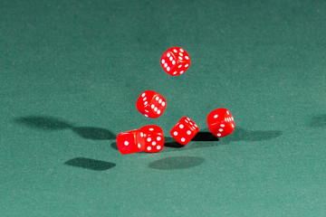 Six red dices falling on a green table