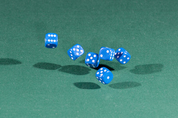 Six blue dices falling on a green table
