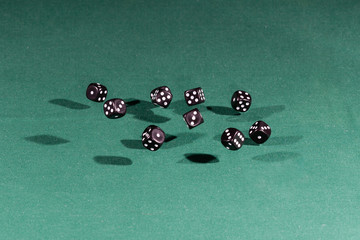 Ten black dices falling on a green table