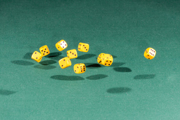 Ten yellow dices falling on a green table