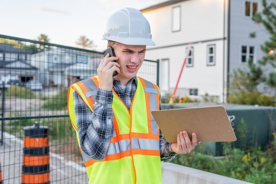Frustrated construction foreman talking with an employee on his cell phone.