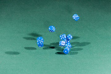 Ten blue dices falling on a green table