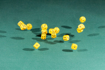 Fifteen yellow dices falling on a green table