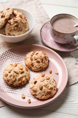 Tasty cookies with cacao drink on white wooden table