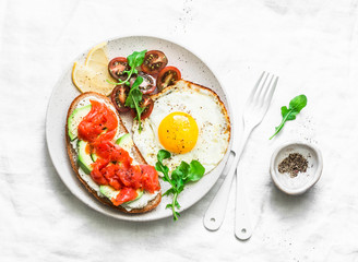 Whole grain bread, cream cheese, avocado, smoked salmon sandwich and fried egg - delicious breakfast, snack, brunch on a light background, top view