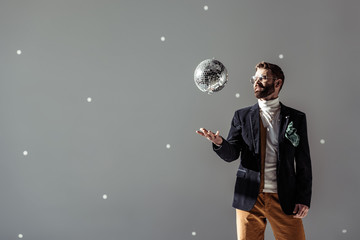 handsome man in glasses throwing up disco ball on grey background