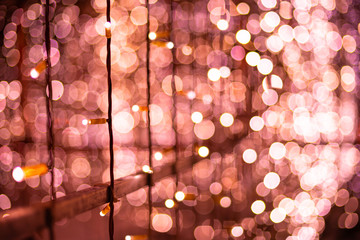 Pink bokeh blurred lights background. Rose garlands decoration for the new year festival celebration.