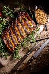 Rustic vintage wooden table, fried juicy pork ribs with meat lying on a bunch of thyme, spices, fork and knife, pepper, rosemary, basil, cherry tomatoes, dark background, mustard are scattered