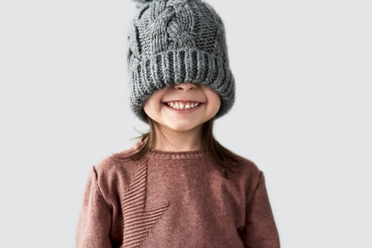 Portrait of funny cheerful little girl hidden the eyes in winter warm gray hat, joyful smiling and wearing sweater isolated on a white studio background.