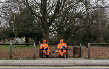 Two council workers wearing bright orange high visibility clothing smile and talk with each other as they take a break from their work at lunchtime on a dull winter's day in London
