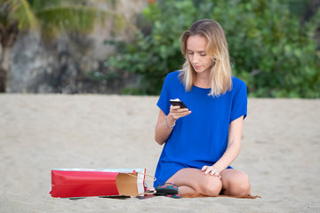 A young blonde girl, on vacation at the beach, sits uses a smartphone. Portrait.