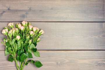 Copy space on a wooden background from boards. A bouquet of small roses.
