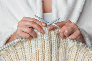 Woman's hands knitting white wool yarn pattern. Closeup horizontal photo. Freelance creative handicraft concept, hobby and lifestyle