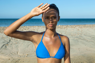 Beautiful, young, black woman wearing a blue bikini at the beach while shading her face with her hand, portrait.