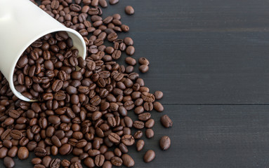 white paper cup and coffee beans on old wooden with soft-focus and over light in the background