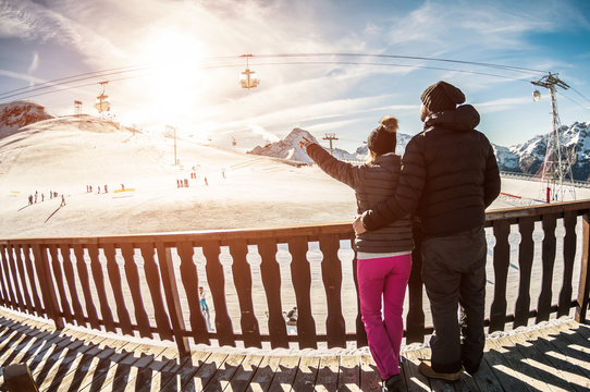 Young couple in winter vacation at snow resort mountain - Skiers tourists relaxing in ski slope chalet - Travel, holiday, relationship and sport concept - Fisheye lens distortion