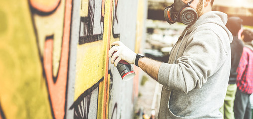 Graffiti artist painting with color spray on the wall for international competition - Urban, street art, millennials generation, mural concept - Focus on his hand