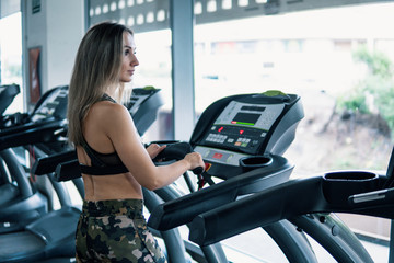 Young fit woman doing running exercise in gym at treadmill speedwalk running road.