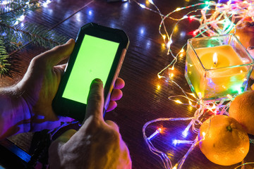 Man hand holding blank green screen mobile smart phone with abstract blurred Christmas light decorated background, home use, wooden table top view