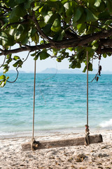 Empty wooden swing on an exotic beach - Ko Kham island, Thailand, Andaman Sea. Wodden swing tied with ropes to a tree with sea in the background.