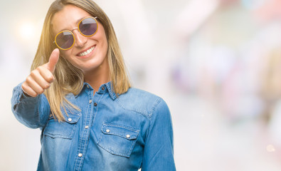 Young beautiful woman wearing sunglasses over isolated background doing happy thumbs up gesture with hand. Approving expression looking at the camera with showing success.