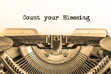 Count your Blessing printed on a piece of paper on a vintage typewriter. writer, journalist.